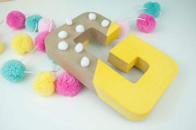 Adding pom poms to paper mache letters. Tutorial with Jen Gallacher from www.jengallacher.com #papermacheletter #spraypaint #pompoms #craftdiy #jengallacher