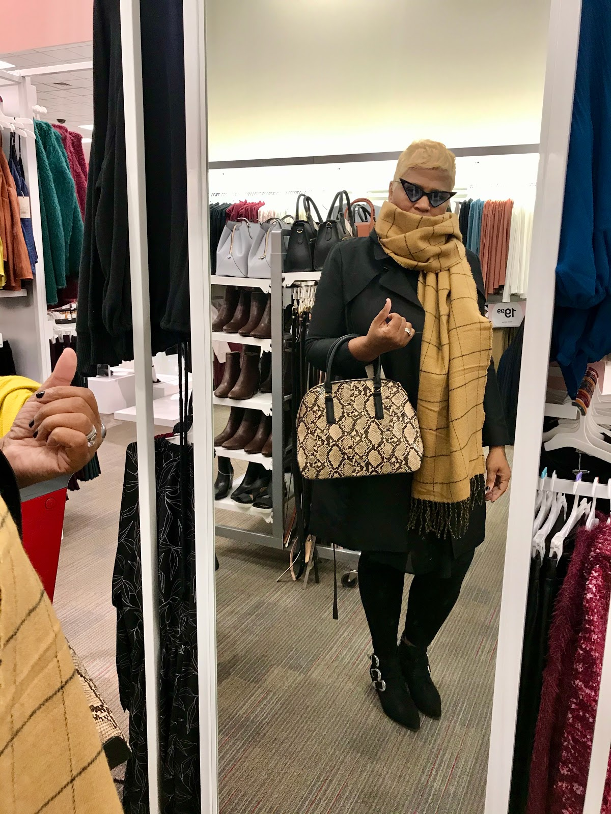 Tangie Bell trying on beige winter scarf and leopard handbag for winter