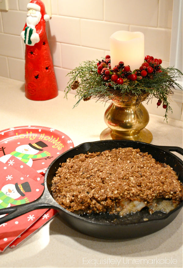 Apple Crisp in a cast iron pan on a table with Santa