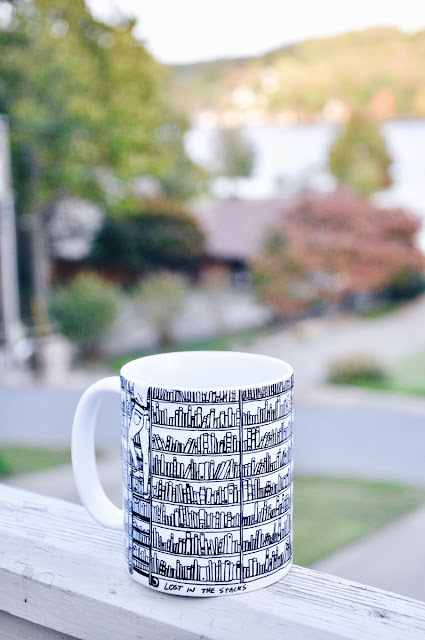 coffee mug on deck by lake
