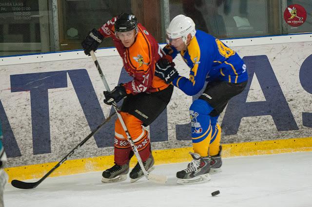 Viens hokejists slido otram nopakaļ gar laukuma bortu