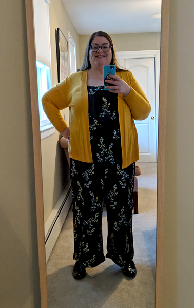 image of me standing in a full-length mirror wearing a black jumpsuit with a floral pattern, a mustard yellow cardigan, and patent black loafers