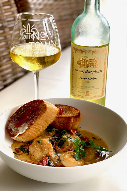 A glass of pinot grigio wine with a beautiful creamy scallop dish