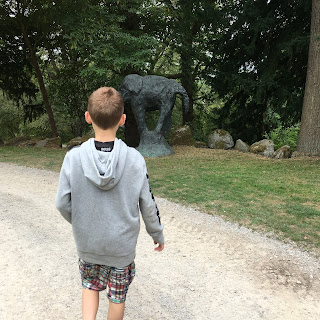 Anthony struggles to remember, imagine of him beside a statue of an elephant in a garden