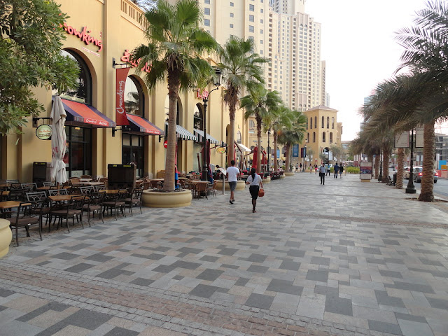 The image shows the walk, JBR. There is a restaurant with outdoor seating, and lots of sky rise buildings in the background. There are also plam trees.