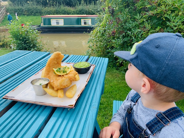 Toddler boy with fish and chips, overlooking the canal