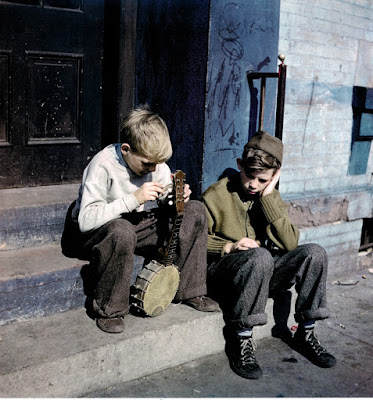color photogrph of 2 boys with a stringless banjo, East Harlem, 1947