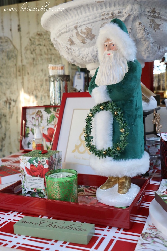A tall Santa dressed in green velvet holds a Christmas wreath in this year's French Country Christmas Event