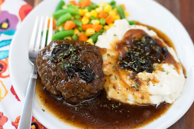 A plate of the Crockpot Salisbury Steak with mashed potatoes and mixed vegetables.