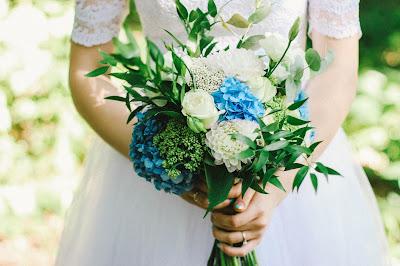 Novia llevando en las manos un ramo con flores azules