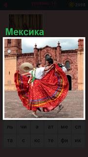 на площади в Мексике танцуют мужчина с женщиной в красном платье