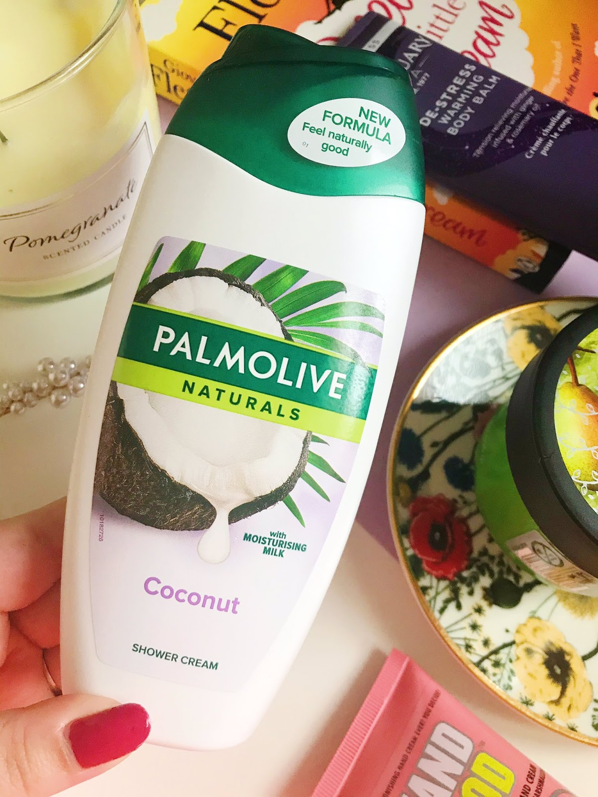 Palmolive Coconut Shower Cream surrounded by candle, book and other beauty products