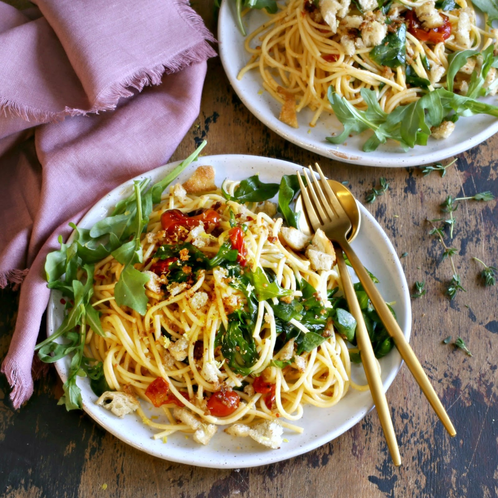 Recipe for a pasta dish with arugula, confit tomatoes and crispy torn bread.