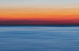 Still from You Cannot Close Your Eyes to New Horizons. Orange sunset over blue sea, looks like a painting
