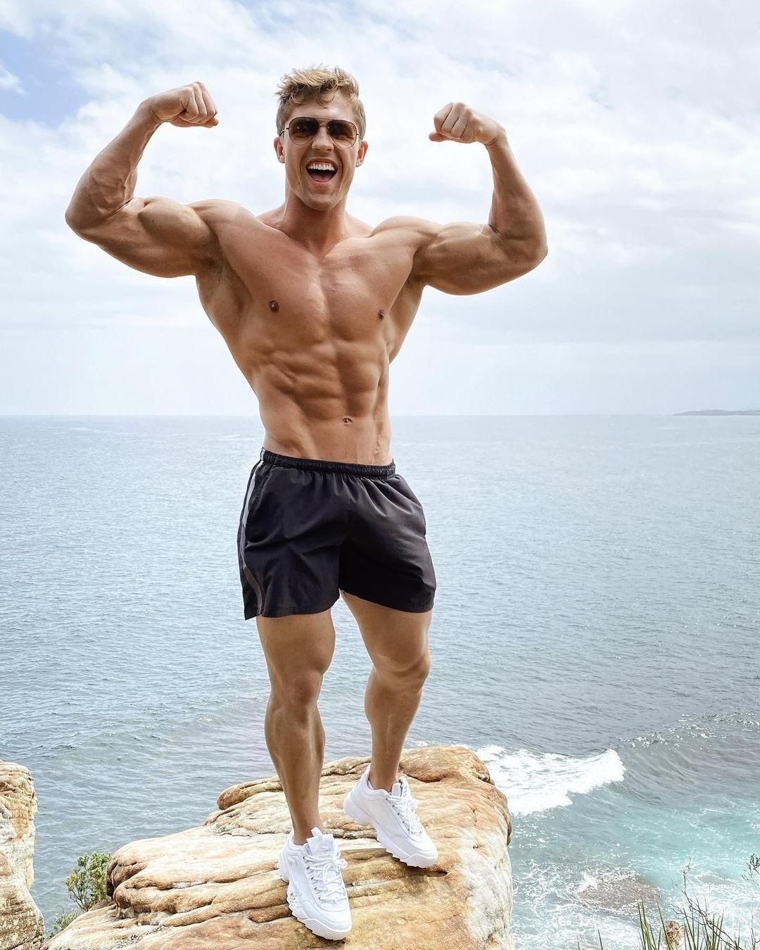 sexy-muscular-shirtless-hunk-smiling-flexing-biceps-strong-body-cocky-straight-sunglasses-bro-amazing-ocean-mountain-view