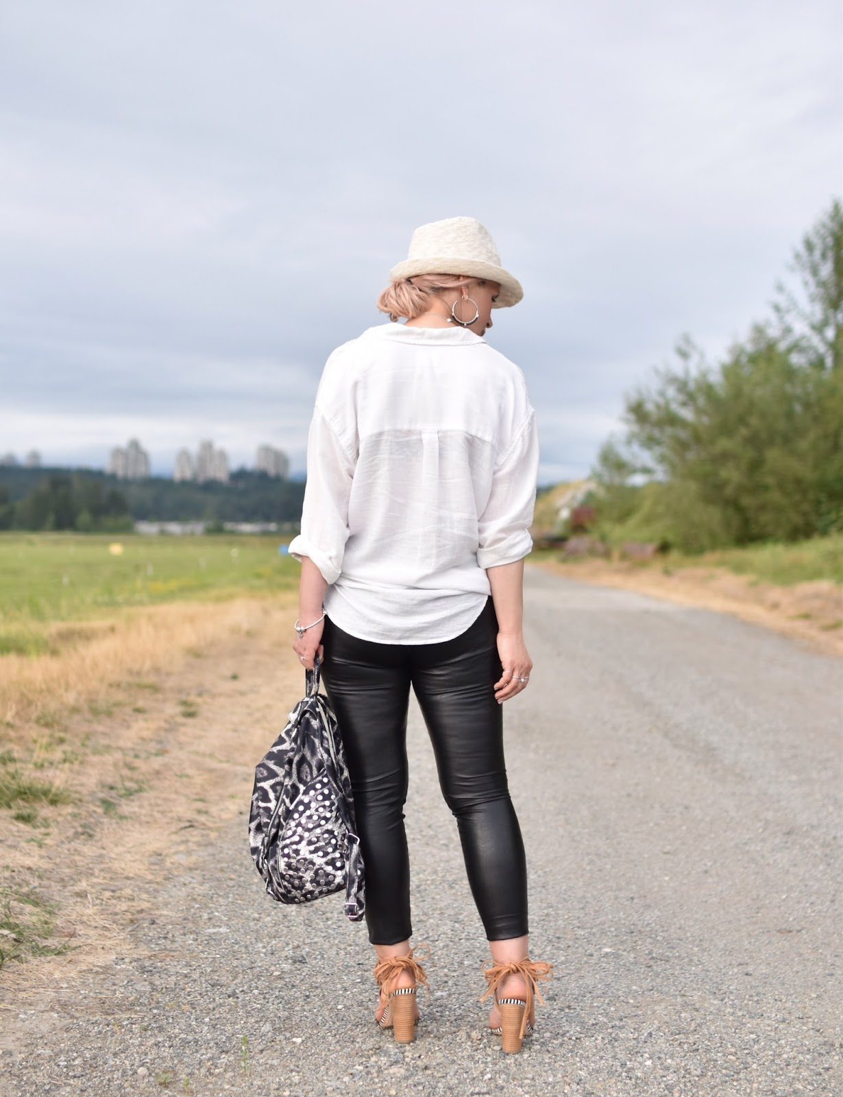 Monika Faulkner personal style inspiration - black vegan leather leggings, oversized white shirt, beaded sandals, straw fedora, leopard-patterned backpack