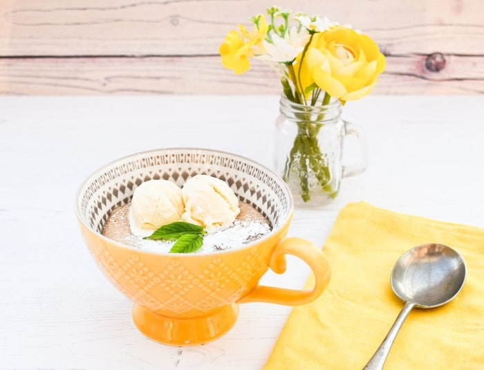 Microwave Apple Sponge Pudding in a large yellow mug topped with vanilla ice cream and mint, sitting beside a yellow napkin and spoon