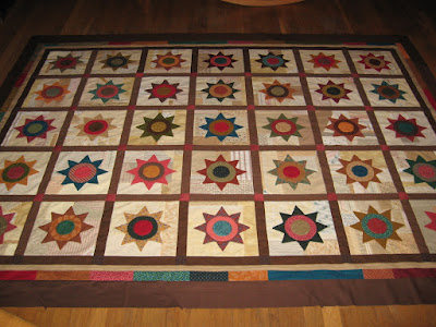 quilt with applique stars on scrappy backgrounds