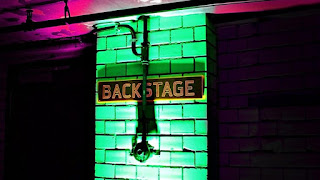 Backstage sign on neon lit wall