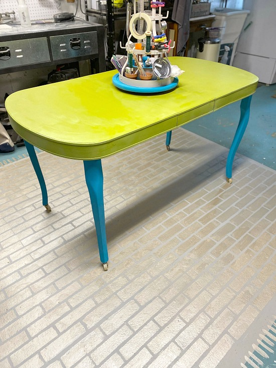 Green and blue painted work table with spinning organizer
