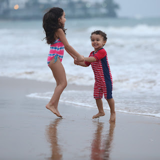 Girl and boy holding hands and jumping in water at beach