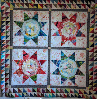 Four red and blue string LeMoyne stars make the center of this medallion surrounded by sashing and an inner border of dark grey print and a double outer border of HSTs in red, blue, brown, and black prints paired with cream and yellowish lights.