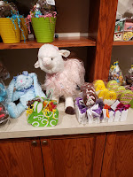 Easter display at Palmer's Candy includes a blue plush rabbit and a white plush lamb sit next to assorted Easter confections, including rice krispie treats that have been dipped in chocolate and then decorated elaborately to look like Easter eggs,and with designs of rabbits, and chicks.