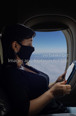 Female passenger in a black protective mask is flying by airplane during the coronavirus pandemic.
