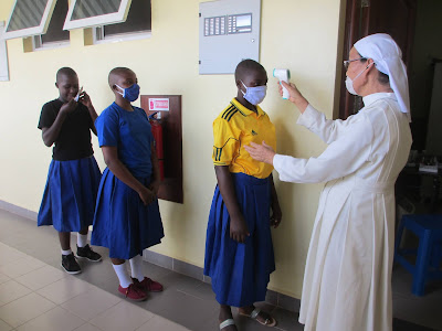 covid charity World villages for children doing Temperature checks on a line of girls in school uniform in  in Tanzania