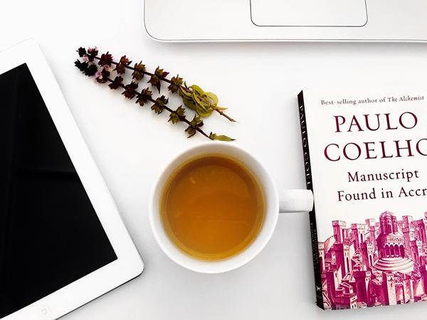 Flatlay fundo branco livro Paulo Coelho, uma xícara de chá e um tablet