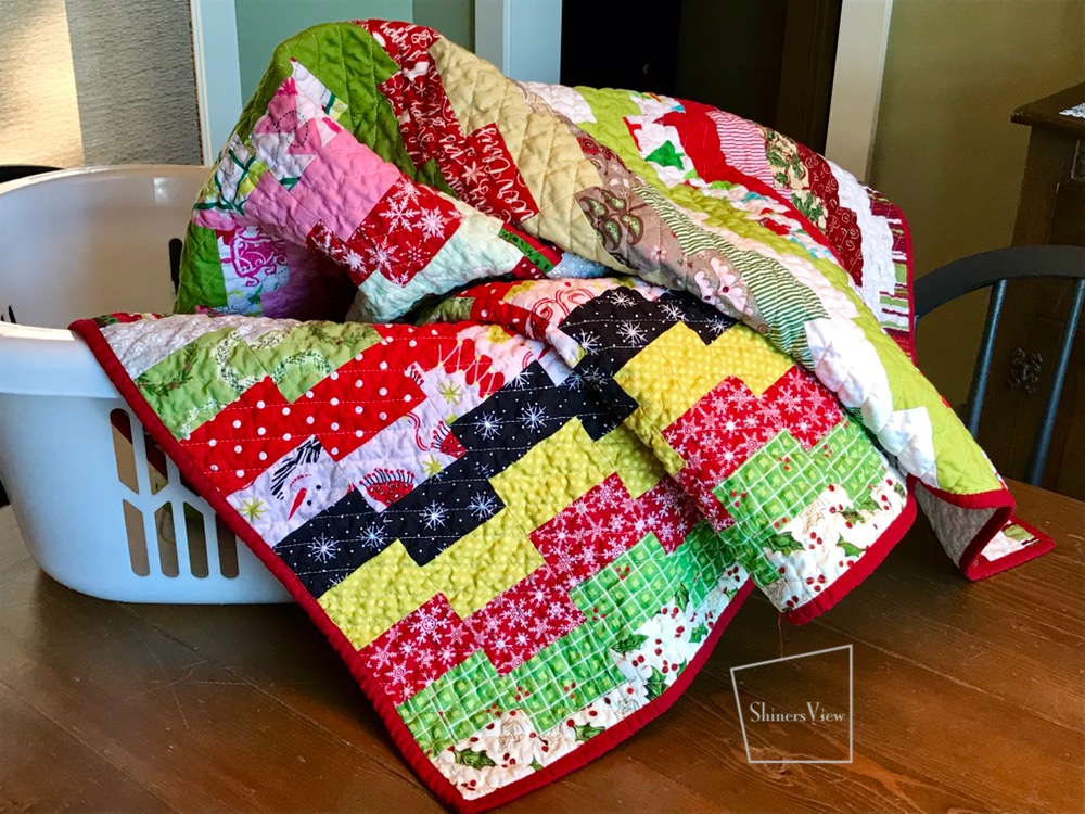 Quilt from christmas fabrics sitting in laundry basket on a dining room table