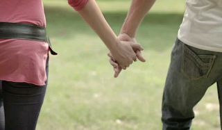 A white man n woman holding hands