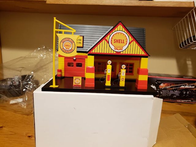 A collectible hard plastic Shell gas station with garage bay, store, and gas pumps.