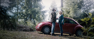 Man and woman in a forest standing in front of a red VW Beetle car