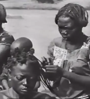 A woman sits as another braids extensions into her hair