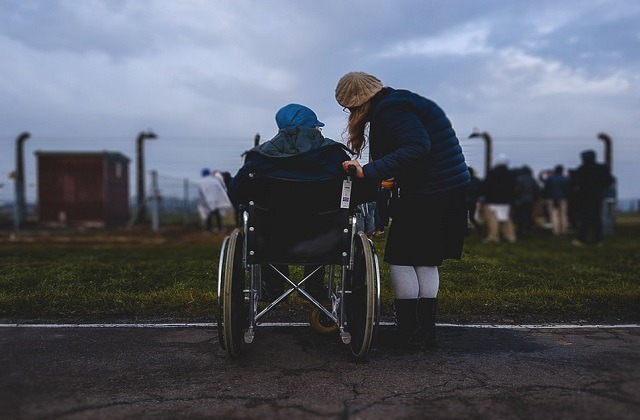 nurse outdoor helping elderly in wheelchair