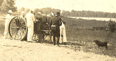 Old black & white photo shows five men of Erie's Life-Saving service with their beach cart, which has large metal wheels and spools of rope. A small black dog is seen to their right.