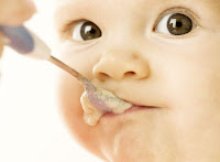 Ağzına kaşıkla mama verilen bir bebek