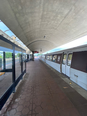 Photo of a Metro platform with an arched roof and a train idling.