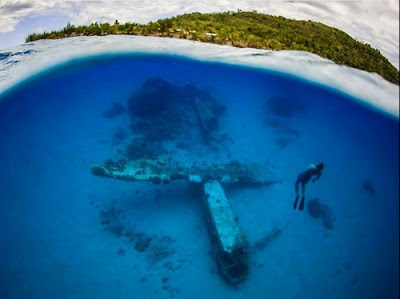 A curved image of a diver swimming by a wreck in a blue lagoon with a white sand beach and green hill. In Vanuatu, South Pacific