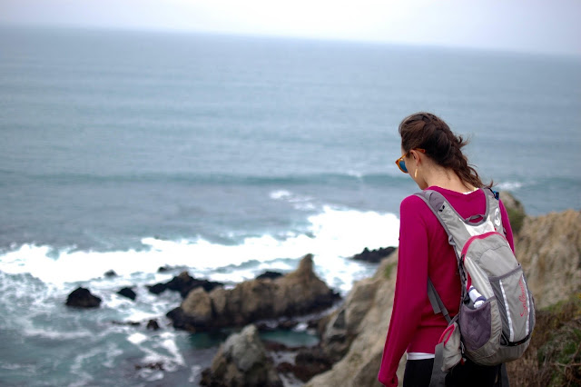 Woman hiking toward Pacific Ocean in California