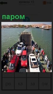 На пароме размещены автомобили и люди для перевозки на другой берег реки