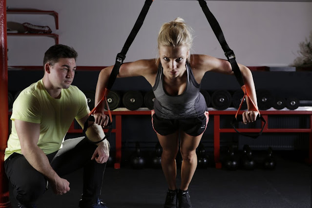 A personal trainer helping a girl workout.