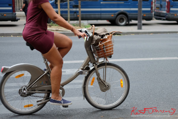 Maroon dress and blue plimsolls, bag in basket; Vélib city bike. Paris photos by Kent Johnson for Street Fashion Sydney.