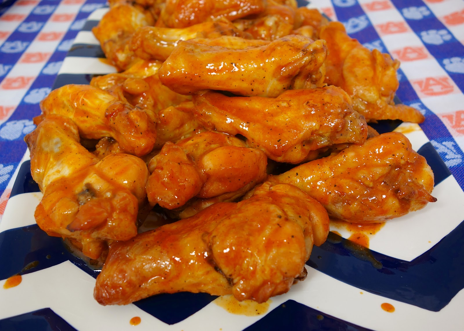 Beer Brined Chicken Wings - CRAZY delicious wings!! Baked not fried!!! Chicken wings marinated in beer, brown sugar, and salt. Bake on a rack in the oven and toss in buffalo wing sauce. Serve with ranch, bleu cheese and celery sticks. Great for parties! #chicken #tailgating #chickenwings #buffalowings