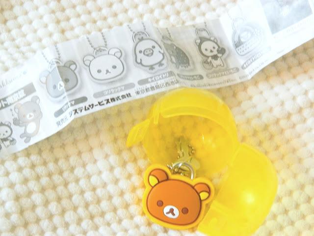 A photo showing a cute little bear shaped lock and key set inside a plastic egg, a gachapon