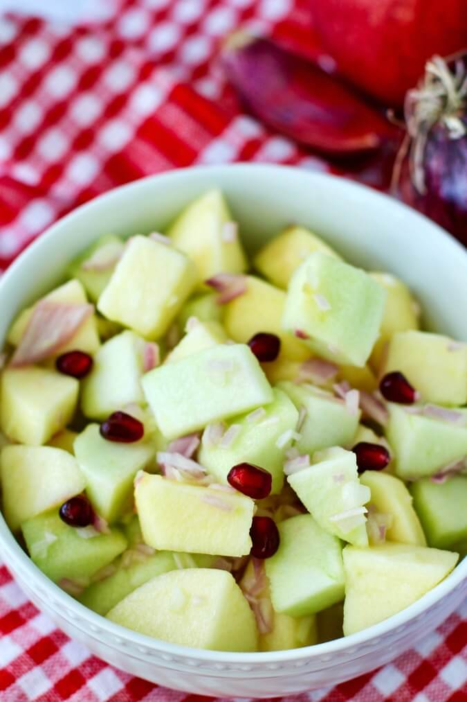 Apple salad with onions, lime, honey, and olive oil in a bowl