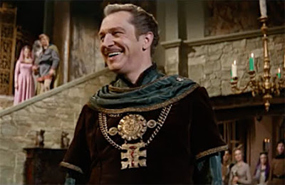 Vincent price wearing burgundy velvet and standing in a castle in Masque of the Red Death