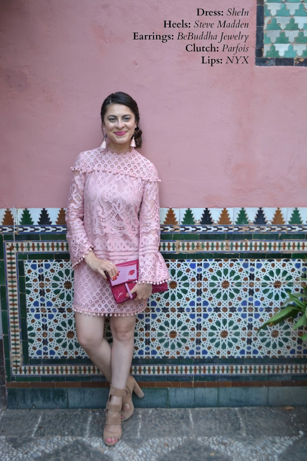 Girl in a pink lace dress standing against a Spanish tiled wall