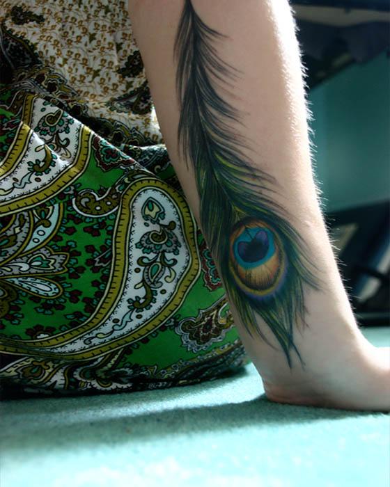 tatuaje de pluma pavo real antebrazo